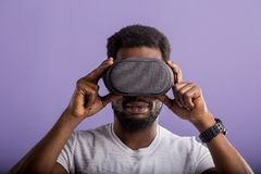 Handsome young African man in VR headset standing against purple background royalty free stock photo