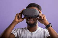 Handsome young African man in VR headset standing against purple background royalty free stock photography