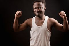 Handsome young Africanaamerican male doing bodybuilding pose. On the black background. taking part in bodybuilding contest Stock Photos