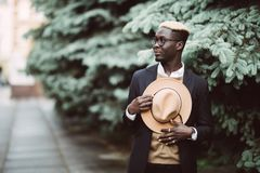 Handsome young Afro American man in casual wear and sun glasses walking outdoors in the street royalty free stock photos