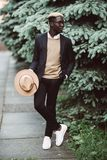 Handsome young Afro American man in casual wear and sun glasses walking outdoors in the street royalty free stock image