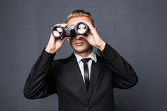 Handsome young american businessman using binoculars in office on gray background Royalty Free Stock Photo