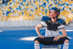 handsome young american football player sitting on bench