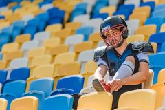 handsome young american football player sitting on tribunes at sports stadium and lacing