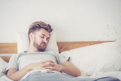 Handsome young american male sleeping in bed at home. Healthcare concept Stock Image