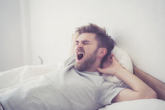 Handsome young american male yawn sleeping in bed at home. Handsome young american male yawn sleeping in bed at home - healthcare concept Royalty Free Stock Photo