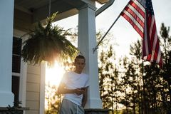 American teenager spends evening in yard. Handsome young american man in 20s chats with his smartphone on a warm summer evening ready to go partying on porch Royalty Free Stock Image