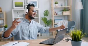 Handsome young Arab enjoying music in headphones working with laptop at home. Handsome young Arab is enjoying music in headphones and working with laptop at home stock footage