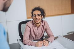 Handsome young architect with building plan talking to colleague. At office royalty free stock images