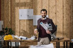 Handsome young architect with coffee to go and rolled blueprints. At workplace stock image