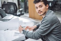 Handsome young architect drawing building plans at office and looking. At camera stock photography