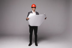 Handsome young architect in protective helmet is studying draft on gray background Stock Photos