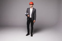Handsome young architect in protective helmet is studying draft on gray background Royalty Free Stock Image