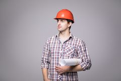 Handsome young architect in protective helmet is studying draft, on gray background. Handsome young architect in protective helmet is studying draft, on gray Royalty Free Stock Images