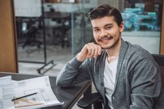 Handsome young architect sitting at workplace with building plans. At office stock images