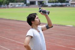 Handsome young Asian fitness man splashing water on his face after run in track of stadium. royalty free stock photography
