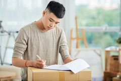 Young man writing in clipboard on carton box royalty free stock photo