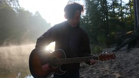 Handsome young asian man playing guitar at coast of forest river at sunrise. Dawn misty fog at background stock video