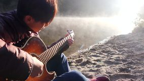 Handsome young asian man playing guitar at coast of forest river at sunrise. Dawn misty fog at background stock video footage