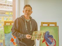 Handsome Young Asian man or water color artist Teaching how to paint royalty free stock photography