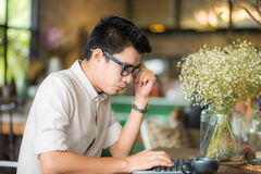 Handsome young asian student man working on laptop and smiling. While enjoying coffee in cafe Royalty Free Stock Images