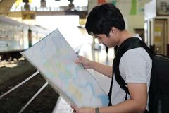 Handsome young Asian tourist with a bag looking at map in train station with copy space background. Handsome young Asian tourist with a bag looking at map in Royalty Free Stock Photos