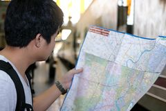 Handsome young Asian tourist exploring map for right direction at the train station. Travel and tourism concept. Selective focus a Stock Images