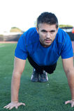 Handsome, young athlete doing push ups Royalty Free Stock Photography