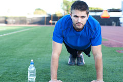 Handsome, young athlete doing push ups Royalty Free Stock Images