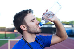 Handsome, young athlete drinking water Royalty Free Stock Photos