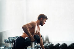 Handsome young athlete working out at the gym Stock Photography