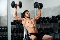 Handsome young athlete working out at the gym royalty free stock images