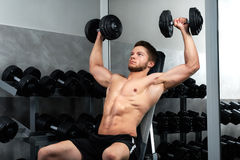 Handsome young athlete working out at the gym royalty free stock photography