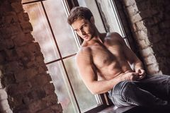 Handsome man in bedroom. Handsome young athletic man with bare torso is looking out the window and thinking while sitting on window-sill Royalty Free Stock Image