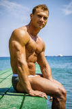 Handsome young, athletic muscle man on pier Royalty Free Stock Photos