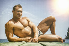 Handsome young, athletic muscle man on pier Royalty Free Stock Image
