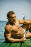 Handsome young, athletic muscle man on pier Stock Photos