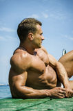 Handsome young, athletic muscle man on pier Stock Photography