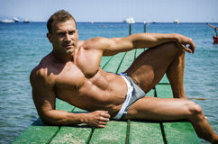 Handsome young, athletic muscle man on pier Royalty Free Stock Photo