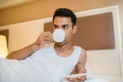 Handsome young awake man drinking cup of coffee in the white bed. Bedroom background Stock Photography