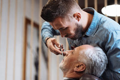 Handsome young barber cutting mustache of senior client with scissors Royalty Free Stock Photo