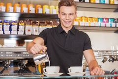 Handsome young barista adding milk. Royalty Free Stock Image