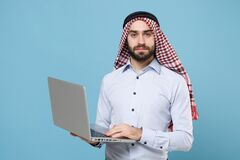 Handsome young bearded arabian muslim man in keffiyeh kafiya ring igal agal casual clothes posing isolated on pastel