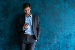 Handsome young bearded business man in office using mobile phone indoors. Handsome young bearded business man in office using mobile phone indoors stock photo