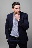 Handsome young bearded businessman in classic suit is adjusting his jacket Royalty Free Stock Images