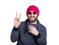 Handsome young bearded hipster in pink knitted hat expresses various emotions and shows different signs the fingers Stock Photos