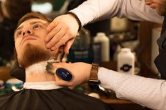 Handsome young bearded man at the barbershop stock photo