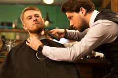 Handsome young bearded man at the barbershop royalty free stock photos