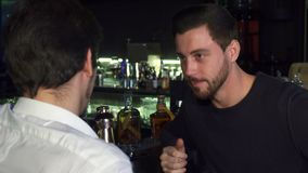 Young male friends talking while having drinks together at the bar. Handsome young bearded man laughing joyfully while talking to his friend at the bar stock video footage