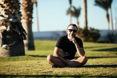 Handsome young bearded man looking aside in sunglasses sitting on the grass under palms on summer vocation. Handsome young bearded man in sunglasses sitting on Royalty Free Stock Images